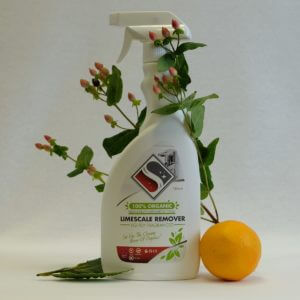 White bottle of limescale remover besides an orange and flowers