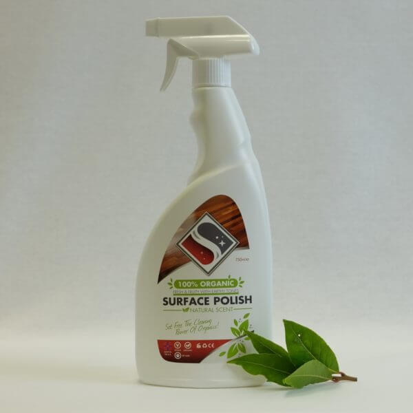 White bottle of organic surface polish behind some leaves